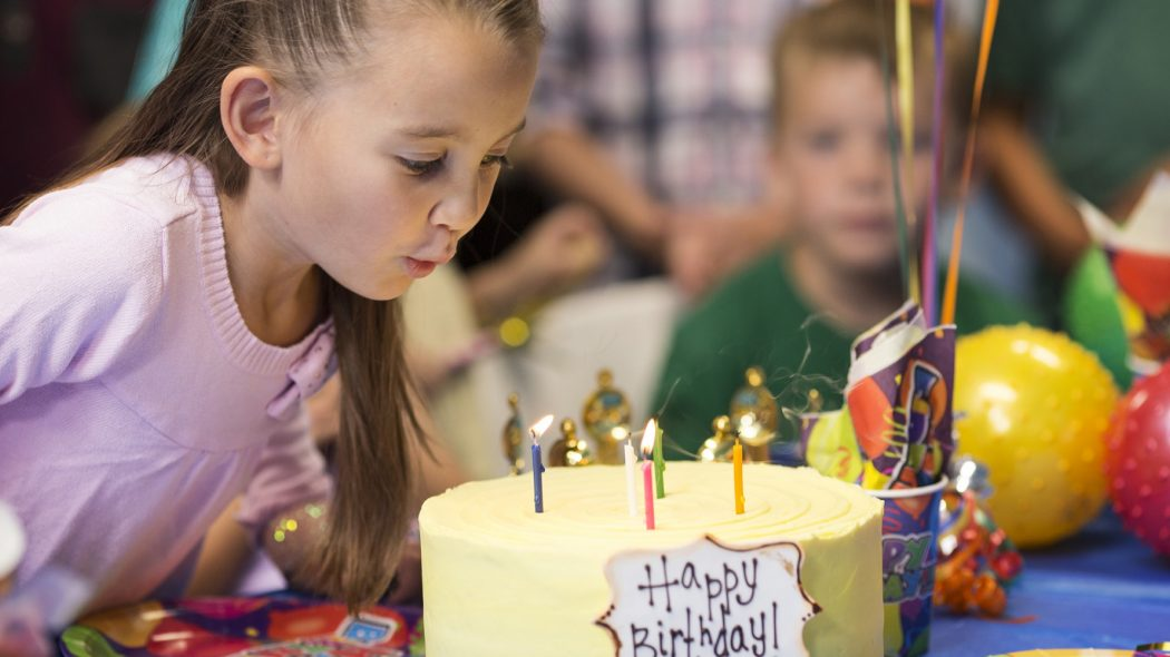 Girl blowing out birthday candles on cake.