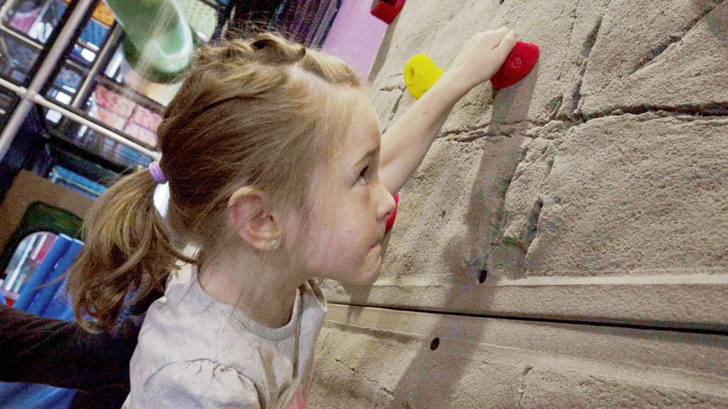 Girl climbing on indoor climbing wall.