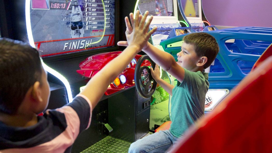Kids high fiving while playing boat racing arcade game.