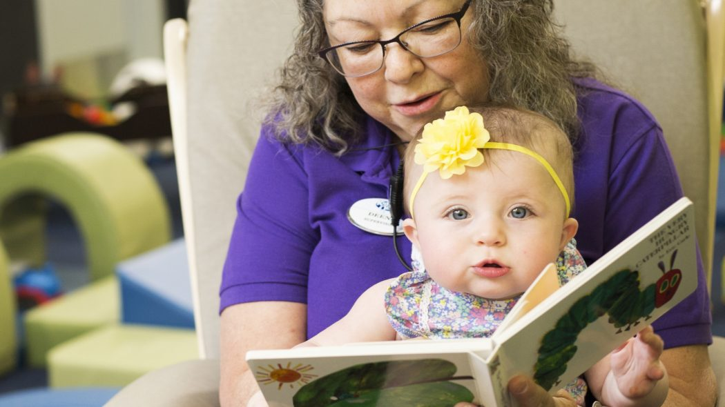 Childcare worker reading book to small toddler.