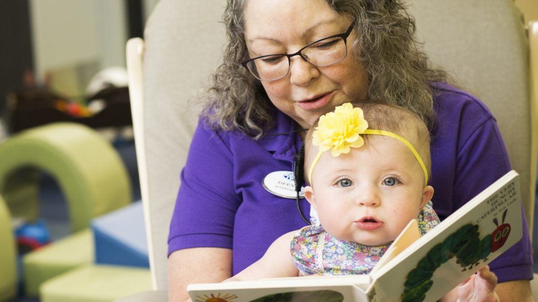 Childcare working reading book to small toddler