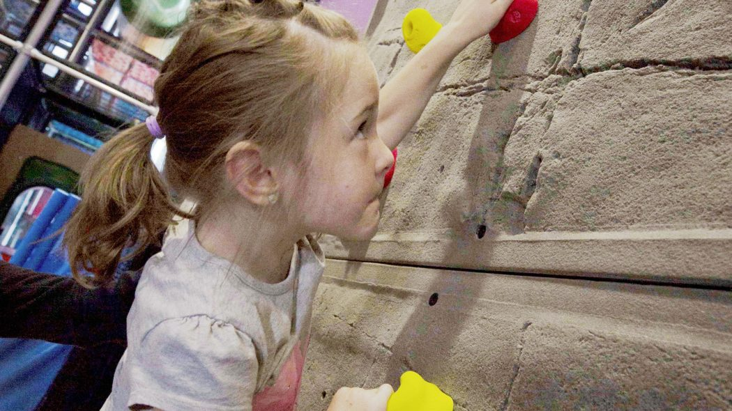 Girl Climbing on indoor climbing wall