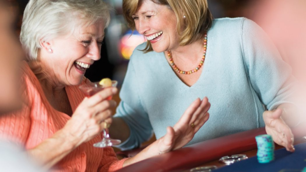 Image of two women laughing at a poker table